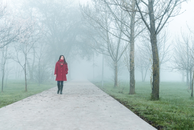 young woman in red walking by city park in fog in the morning